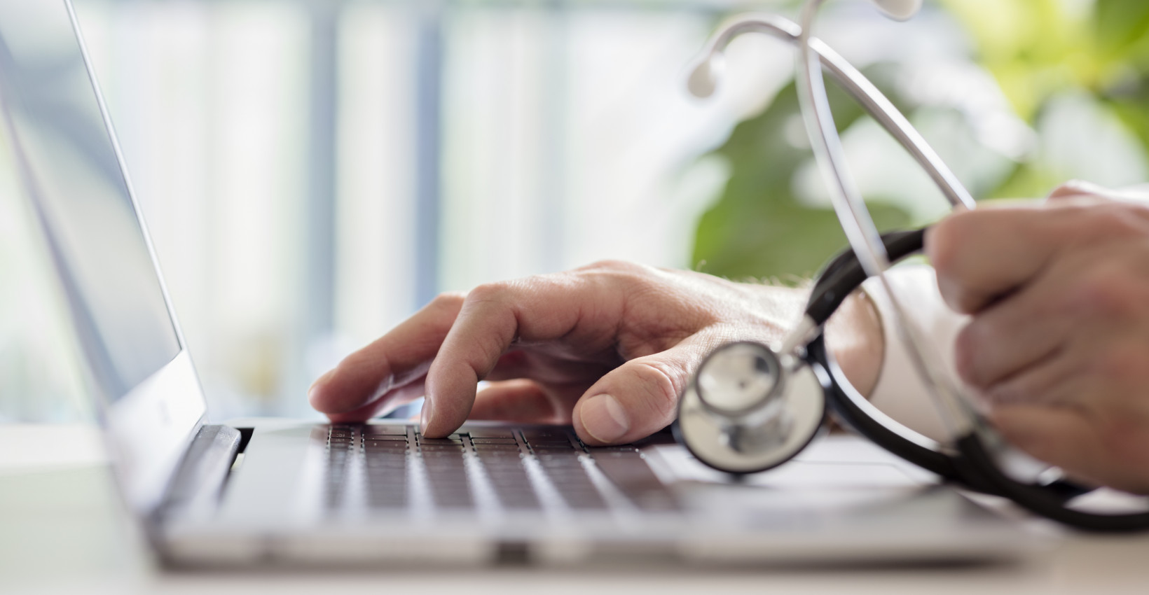 Hand on keyboard with stethoscope