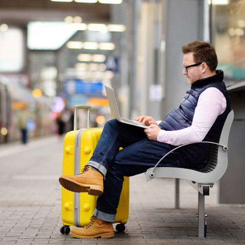 Man sitting with suitcase, waiting for departure