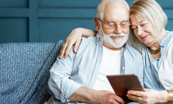 Two older folks looking at a tablet
